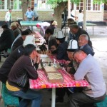 Locals in Osh playing chess and ping pong, wearing traditional Kyrgyz hats