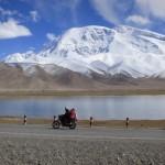 Locals riding a motorcycle at Karakul Lake