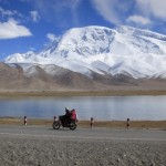 Locals riding a motorcycle at Karakul Lake