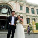 Newlywed couple posing in front of the Saigon post office.
